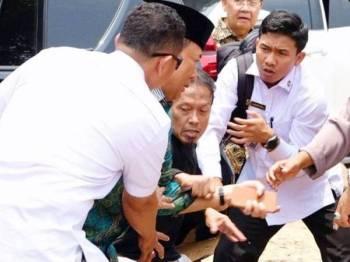 Menteri Keselamatan Indonesia, Wiranto (dua dari kiri) cuba mengelak tikaman seorang lelaki yang meluru ke arahnya.