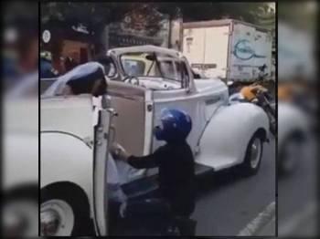 Penunggang yang berpakaian hitam dengan topi keledar berwarna biru, berjalan ke arah kenderaan pengantin perempuan dan membuka pintu kereta antik dan berlutut merayu agar dia tidak meneruskan upacara perkahwinan. - Foto Agensi