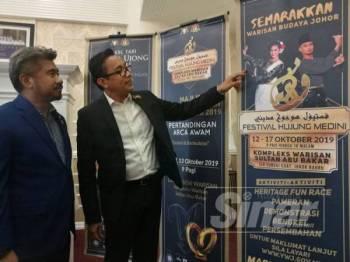 Mohd Khuzzan menunjukkan bunting promosi festival selepas sidang media di Kompleks Warisan Sultan Abu Bakar sambil diperhatikan Sharil di Kompleks Warisan Sultan Abu Bakar semalam.