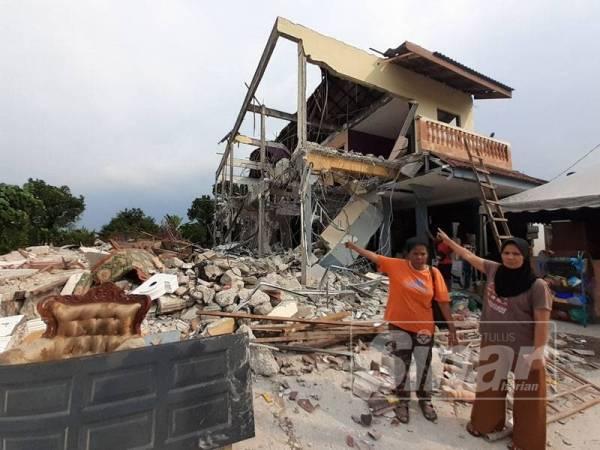 Penduduk menunjukkan rumah mereka yang dirobohkan semalam.