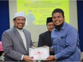 Satiful menyampaikan sijil pelantikan kepada salah seorang ahli jawatankuasa masjid yang dilantik. - Foto Media ADUN Paka