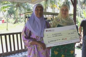 FAIZA (kanan) bersama penerima sumbangan dalam program Bersamamu.