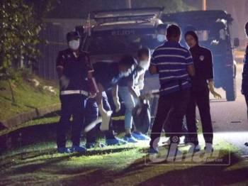 Anggota forensik mengangkat beg plastik berisi keretan mayat di Kampung Ladang, Krubong, Melaka, semalam.