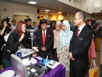 DR Boon Chye (kanan) ketika melawat pameran berkaitan mata.