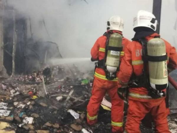 Anggota bomba bertungkus-lumus memadam kebakaran kilang terbabit sebelum api berjaya dikawal bagaimanapun 80 peratus struktur bangunan berkenaan musnah terbakar. Foto: Ihsan bomba
