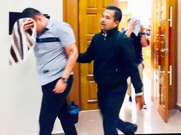 Muhammad Rayyan John (depan) dan Stenley Blasius diiringi pegawai SPRM keluar dari kamar mahkamah selepas mengaku tidak bersalah.