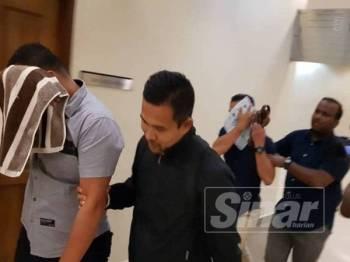 Muhammad Rayyan John (depan) dan Stenley Blasius diiringi pegawai SPRM keluar dari kamar mahkamah selepas mengaku tidak bersalah di Mahkamah Sesyen Kuantan hari ini atas tuduhan menerima suapan daripada seorang lelaki Mac lalu.