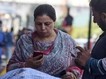 Penduduk Kashmir menggunakan telefon bimbit miliknya selepas talian komunikasi dipulihkan semalam. - Foto AGENSI