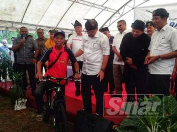 Wan Rosdy menyampaikan hadiah kepada pemenang cabutan bertuah sempena Majlis Ramah Mesra Bersama Masyarakat Orang Asli di Padang Awam Pos Iskandar di sini.