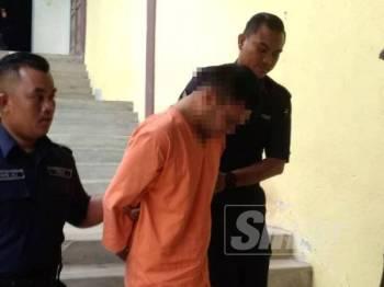 Suspek ketika dibawa keluar selepas dikenakan tahanan reman selama tiga hari bermula hari ini.