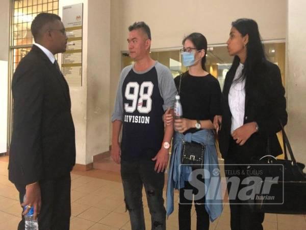 Tat Meng (dua dari kiri) ketika keluar dari Mahkamah Majistret Petaling Jaya.