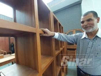 Mohamad Sultan Bhat menunjukkan antara perabot yang dihasilkan daripada kayu jati bermutu tinggi yang dijualnya.