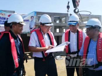 Tza Tzin (dua dari kiri) ketika meninjau lokasi melabuhkan tukun bersama Ketua Pengarah Perikanan, Datuk Munir Abd Mohd Nawi (kiri) dari atas tongkang di Pulau Lima.