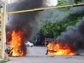 Kenderaan terbakar di bandar Culiacan, Mexico susulan pertempuran sengit kumpulan bersenjata dengan pasukan keselamatan yang membawa kepada penangkapan anak lelaki raja dadah Mexico, Joaquin 'El Chapo' Guzman semalam. - Foto AFP