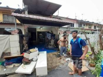 Penduduk sedang membersihkan rumah akibat banjir kilat yang melanda di Taman Sri Muda di sini petang semalam.