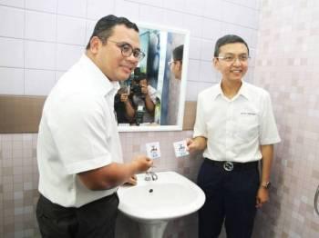 Amirudin memasang bidal pada paip air ketika melawat tapak pameran dengan ditemani Suhaimi. Foto: ROSLI TALIB