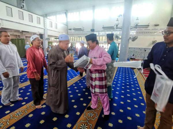 Mohd Anuar (dua dari kanan) menyerahkan sumbangan al-Quran kepada jemaah haji dalam majlis tersebut semalam.