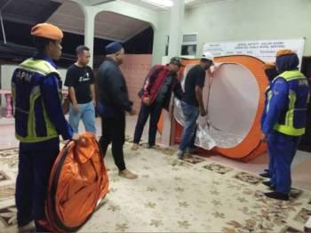 Anggota APM membantu menyiapkan khemah untuk kegunaan mangsa yang dipindahkan ke PPS di surau Kampung Kuala Repas malam tadi. - Foto APM