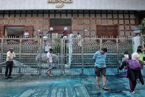 Beberapa penduduk turut membantu membersihkan kesan pewarna biru di hadapan pintu masuk Masjid Kowloon tersebut. - Foto AFP