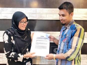 Shaiful Afzan (kanan) menyerahkan surat permohonan maaf kepada Majdah.
