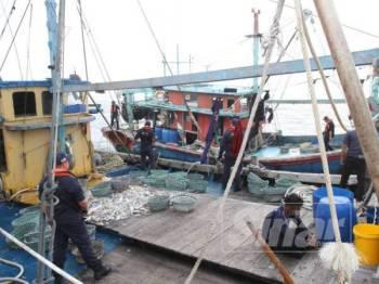 Penguatkuasa APMM Selangor menggeledah dan memeriksa sebuah bot nelayan tempatan setelah mengesan pekerja di atas adalah warga asing. - FOTO ASRIL ASWANDI