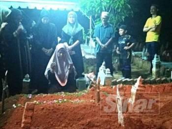 Ibu mangsa, Fatimah Latiff berdoa di tepi pusara anak dan cucunya di Tanah Perkuburan Islam Cheng Setia di sini, tadi.