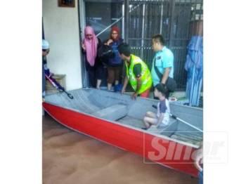 Anggota Pasukan Bomba Sukarela membantu memindahkan mangsa banjir dari rumah mereka ke PPS yang dibuka.