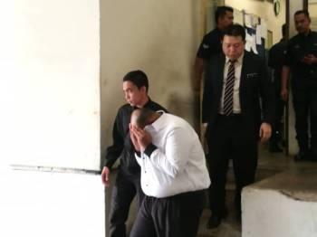 Suspek diiringi pegawai SPRM keluar dari lokap mahkamah selepas perintah reman dikeluarkan.
