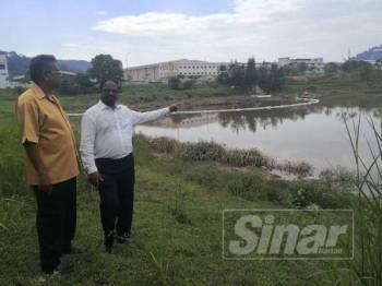 Veerapan (kanan) menunjukkan kolam takungan JAS yang tercemar.