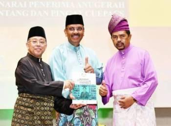 Ali (tengah) melancarkan buku Biografi Perjuangan Cuepacs sambil disaksikan Azih (kiri) dalam Majlis Makan Malam sempena Ulang Tahun Ke-62 Cuepacs di sini malam ini.