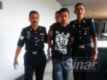 Shahrul Nizam diiringi anggota polis selepas keluar dari Mahkamah Majistret Ayer keroh, di sini, hari ini.