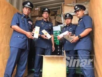 Mohammad Hamiddan (kiri) bersama petugas Kastam Johor menunjukkan antara barangan rampasan yang diperoleh dalam operasi itu.