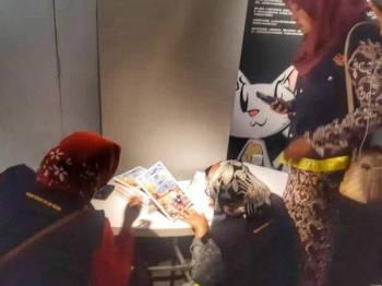 Anggota KDN sedang memeriksa komik ketika serbuan di muzium tersebut pagi tadi.