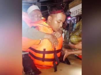 Anggota APM Baling mendokong seorang warga emas demi membantu memindahkan mangsa selepas air naik di daerah Baling.