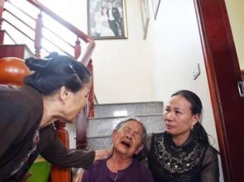 Tran Thi Hue (tengah), nenek kepada Le Van Ha, 30, yang dikhuatiri salah seorang daripada 39 mangsa yang ditemui maut dalam kontena sejuk beku di Britain Rabu lalu.ditenangkan ahli keluarga di rumah mereka di wilayah Nghe An. - Foto AFP
