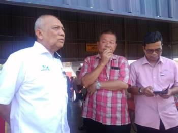 Mohd Soffi (kiri) bersama Fook Wing (tengah) ketika perjumpaan bersama mangsa kebakaran di kampung terbabit hari ini.