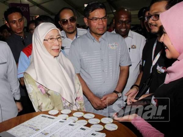 Wan Azizah (kiri) beramah mesra dengan seorang pempamer yang menjayakan Karnival Kempen Beli Barangan Malaysia Peringkat Kebangsaan di Dataran Angsana, Johor Bahru.