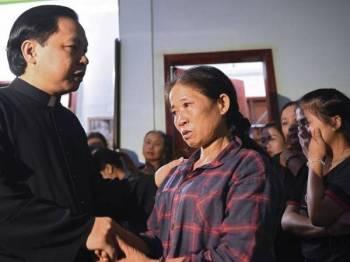 Salah seorang ibu mangsa ditenangkan ahli keluarganya di rumah mereka di wilayah Nghe An. - Foto AFP
