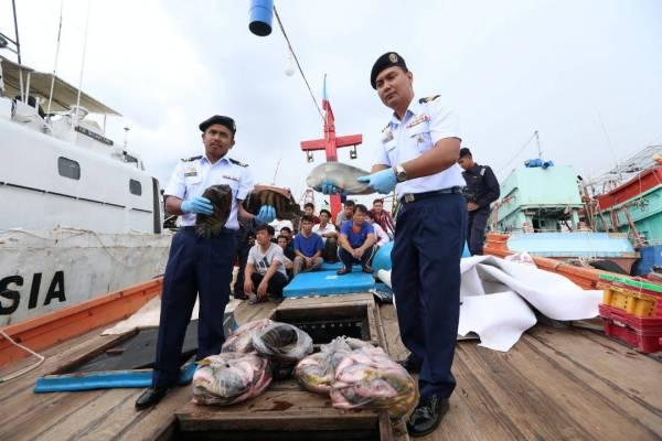 Rashidilhadi (kanan) menunjukkan sebahagian daripada hasil tangkapan laut yang dirampas selepas sidang media di pejabat APMM Terengganu hari ini.