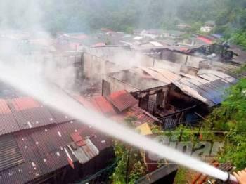 Anggota bomba sedang melakukan kerja-kerja memadamkan kebakaran.