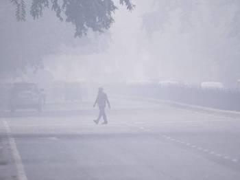 Seorang lelaki melintasi jalan raya di tengah-tengah jerebu beracun yang melanda New Delhi hari ini. - Foto: AFP