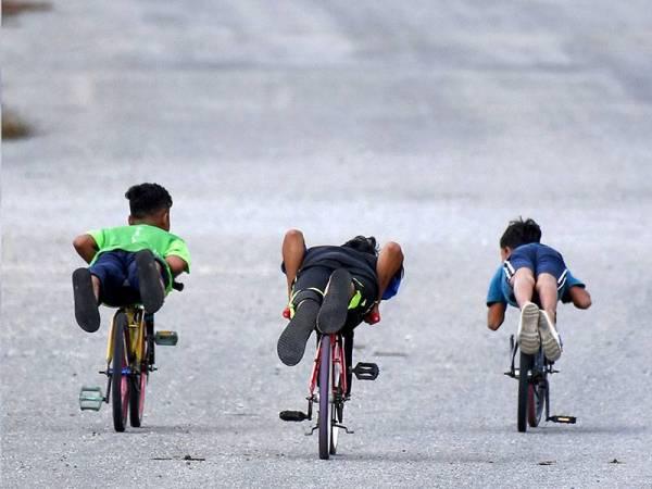 Tiga remaja dan kanak-kanak berlumba sesama sendiri ketika tinjauan di Bukit Besar baru-baru ini. - Foto Bernama