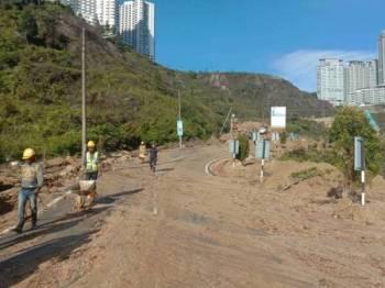 Kerja-kerja pembersihan laluan yang terjejas akibat kejadian tanah runtuh petang semalam masih dijalankan. - Foto Jabatan Bomba dan Penyelamat