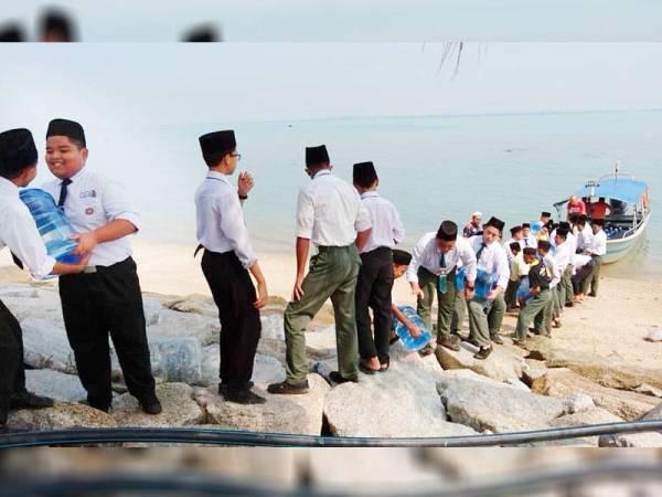 Pelajar sekolah Menengah Agama dan Tahfiz al- Quran Jabatan Agama Islam Melaka (SMATQ, JAIM) Pulau Besar bergotong-royong mengangkut bekalan air bersih dari sebuah bot laju.