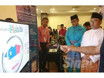 Adly (dua dari kanan) diiringi Hasim (kiri) mendengar penerangan mengenai aplikasi pintar Respons Rakyat Melaka di Hotel Pantai Puteri, Tanjung Kling hari ini.