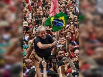 Bekas presiden Brazil, Luiz Inacio Lula da Silva (Lula) mengibarkan bendera Brazil ketika diusung penyokong setianya dalam perhimpunan di Sao Bernardo do Campo semalam. - Foto AFP