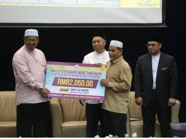 Mohd Nor (kiri) menyerahkan replika cek bayaran kepada salah seorang imam, sambil diperhatikan Mat Azmi (dua dari kiri).