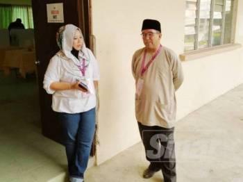 Badhrulhisham (kanan) berbual bersama calon Bebas, Faridah Aryani Abdul Ghaffar di IPD Pontian, lokasi pengundian awal bagi PRK Parlimen Tanjung Piai.