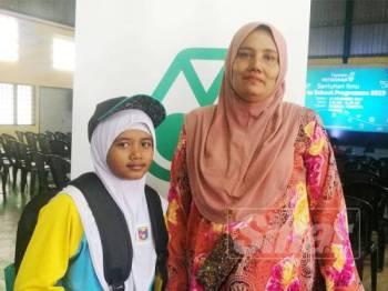 Maznah bersama anaknya, Nor Syazliana yang menerima bantuan peralatan sekolah hari ini.
