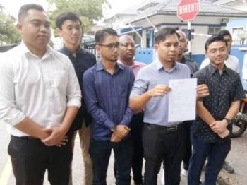 Muhammad Azizi menunjukkan laporan polis terhadap kenyataan Lokman Noor Adam.